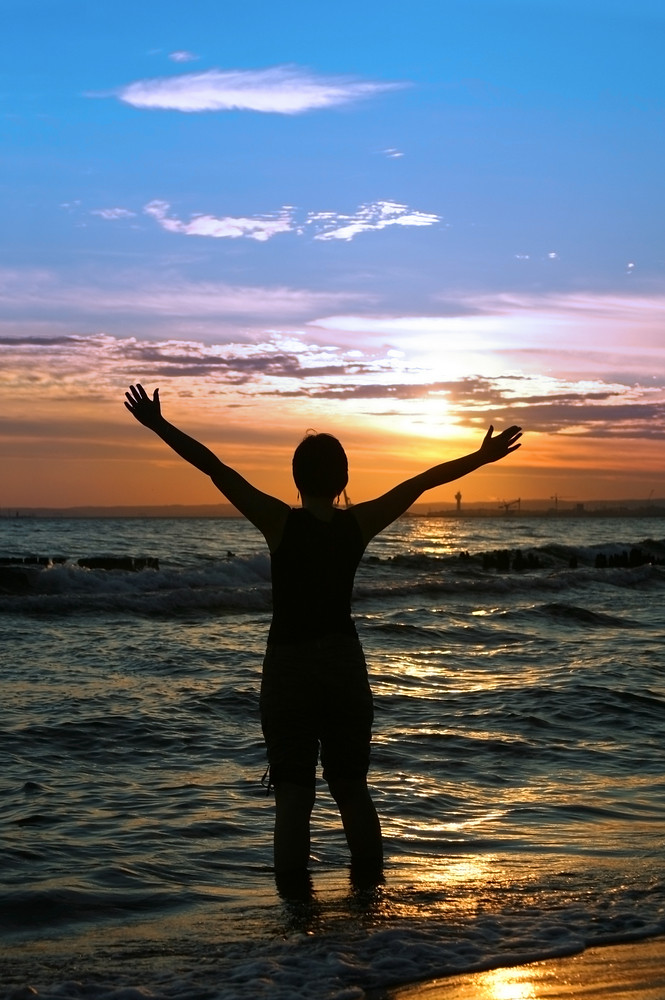 vibrant, healthy woman standing at seashore, raising arms at sunset