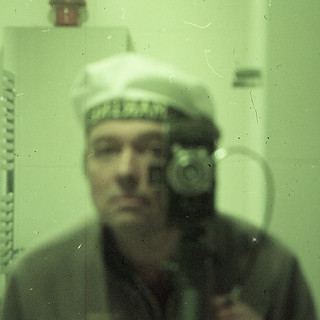 reflected self-portrait with Agfa Billy Compur camera and marine's hat (square crop)