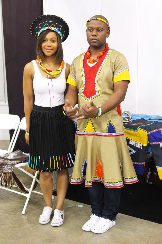 Zulu-hat,-necklace,-white-tank-top,-beaded-skirt,-beaded-necklace-&-converse-Mens-colourful-dress-over-jeans-&-trainers