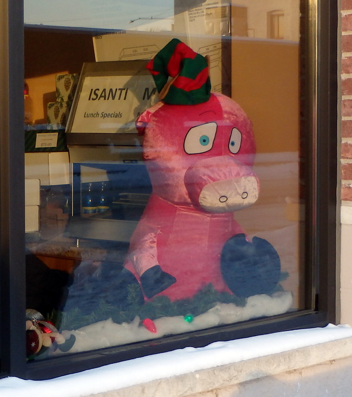 giant stuffed pink pig with a small green-and-red elf hat
