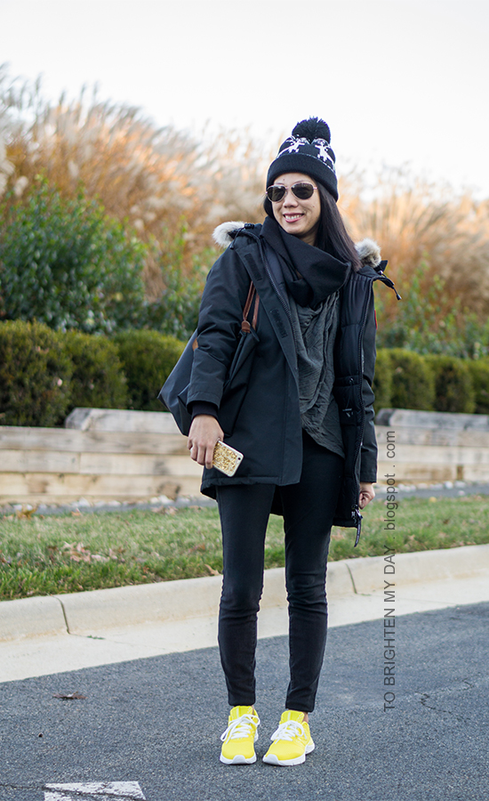 reindeer knit pom beanie, black parka, dark gray draped top, black skinny jeans, yellow sneakers
