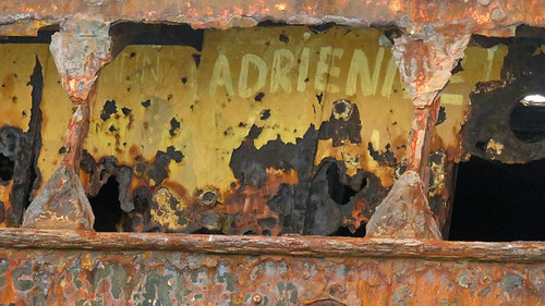 Adrienne paints her name on a rusting shipwreck on the Aran Island of Inisheer in Ireland