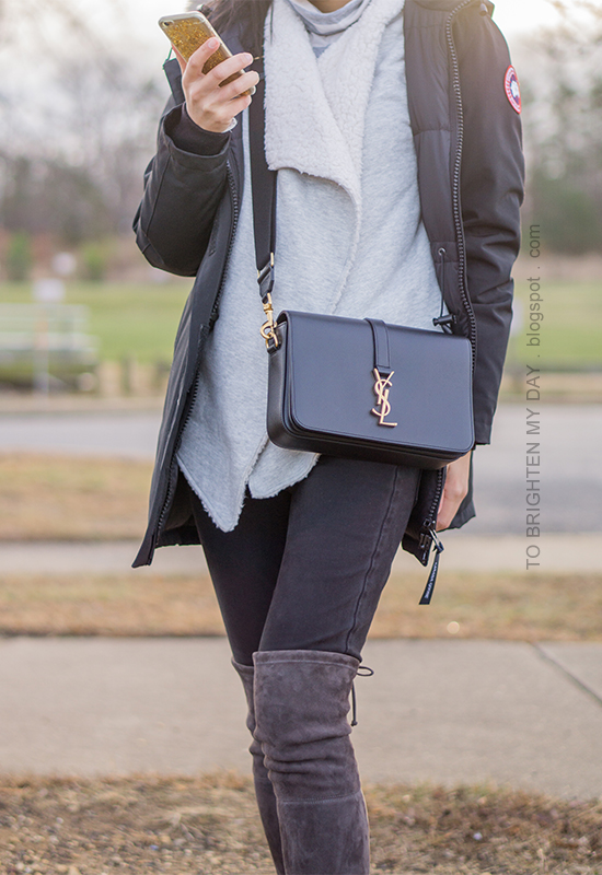 black parka, gray striped turtleneck, gray sherpa lined open cardigan, black crossbody bag, gray over the knee suede boots