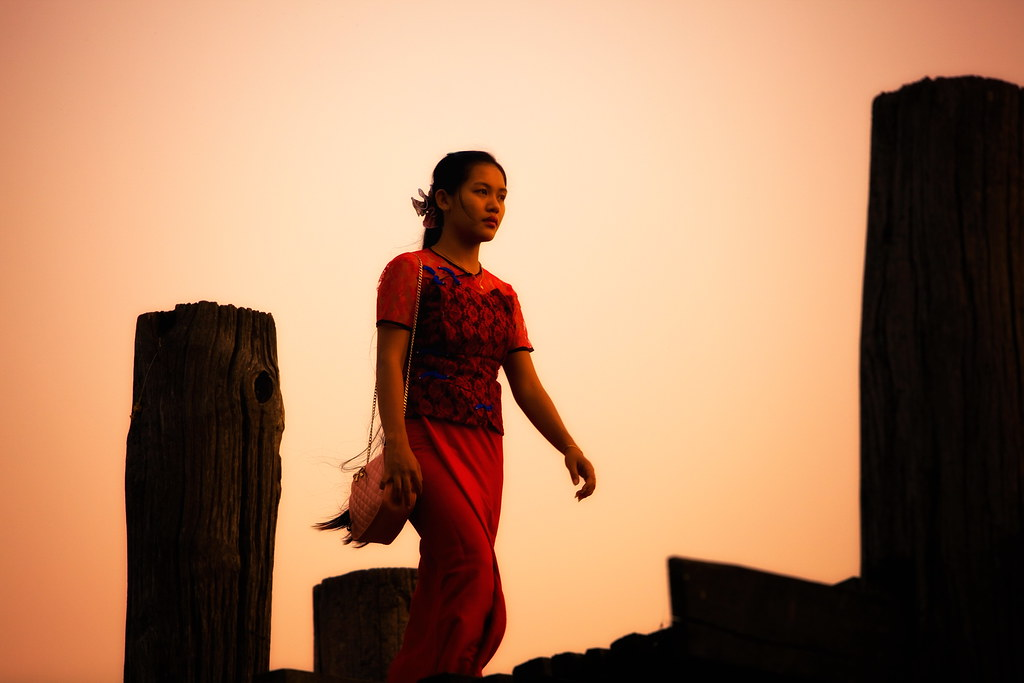 A Burmese Woman Crosses The U Bein Bridge At Sunset