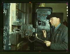 Hump master in a Chicago and Northwestern railroad yard operating a signal switch system which extends the length of the hump track. He is thus able to control movements of locomotives pushing the train over the hump from his post at the hump office; Chic | by The Library of Congress