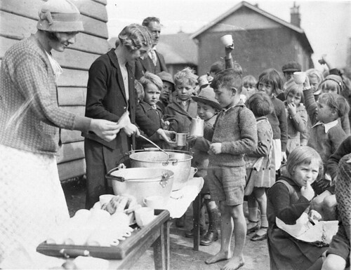 Schoolchildren line up for free issue of soup and a slice of bread in the Depression, Belmore North Public School, Sydney, 2 August 1934 / Sam Hood | by State Library of New South Wales collection