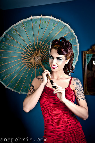 Pretty Tattooed Redhead Pinup model wearing a red swimsuit and a parasol | by tibchris