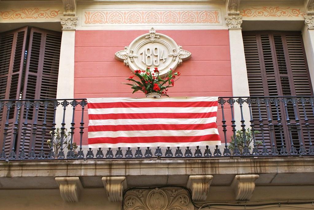 Façade art nouveau du quartier de Gracia avec fleurs et drapeaux catalans.
