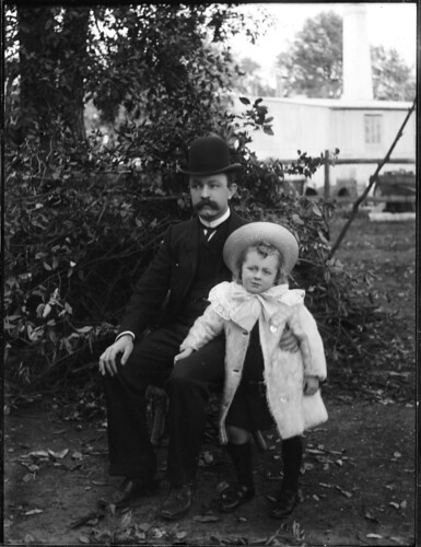 Portrait of seated man in dark suit with small girl standing beside him | by Powerhouse Museum Collection