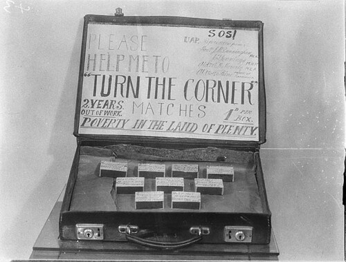 "Unemployed match-seller's sign: Please help me to ""turn the corner"". 2 years out of work. Matches 1d per box. Poverty in the land of plenty. SOS! UAP, Sydney, ca. 1935 / Sam Hood 