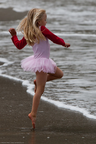 Cute Little Girl in Pink Dances on  Beach during the Kite Festival. | by mikebaird