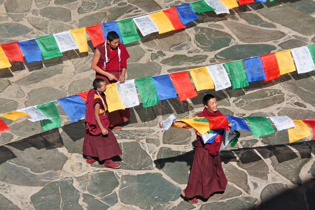 Monks unwinding prayer flags