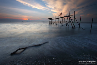 a driftwood, a jetty and a fisherman | by acidsulfurik
