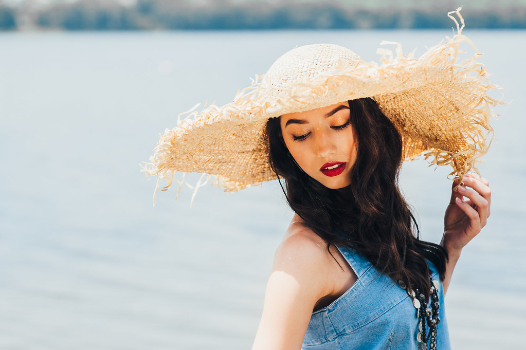 beautiful girl on the lake in big hat