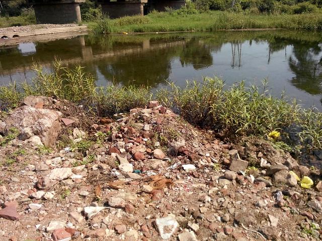 बाग की बाघनी नदी में डाला गया टूटे मकान का मलबा