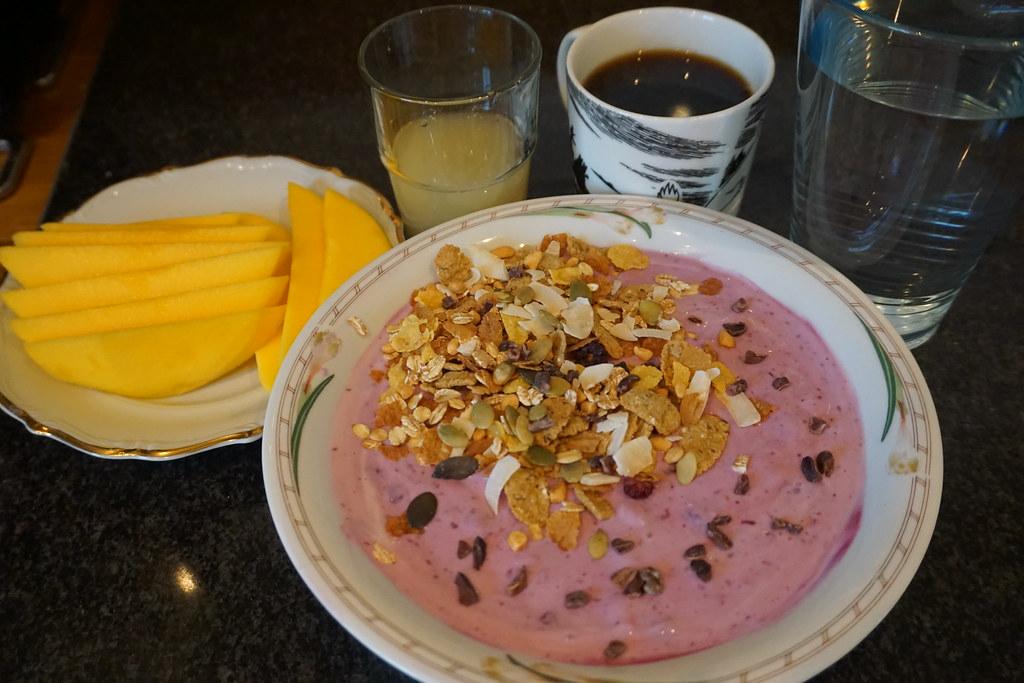 Yoghurt med blåbär, banan, kvarg, flingor, frön, müsli och färskmango, ingefärsshot, vatten och kaffe