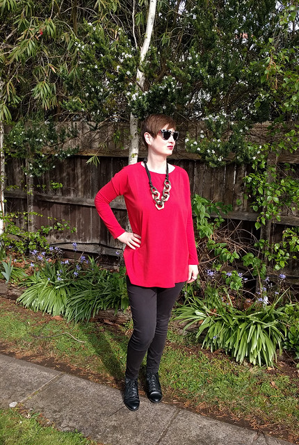 A woman wears Tessuti Mandy Boat Tee in red with black pants
