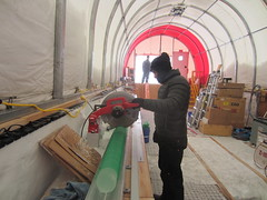 Murat Aydin cuts a 2-meter-long piece of the brittle ice into 1-meter-long sections