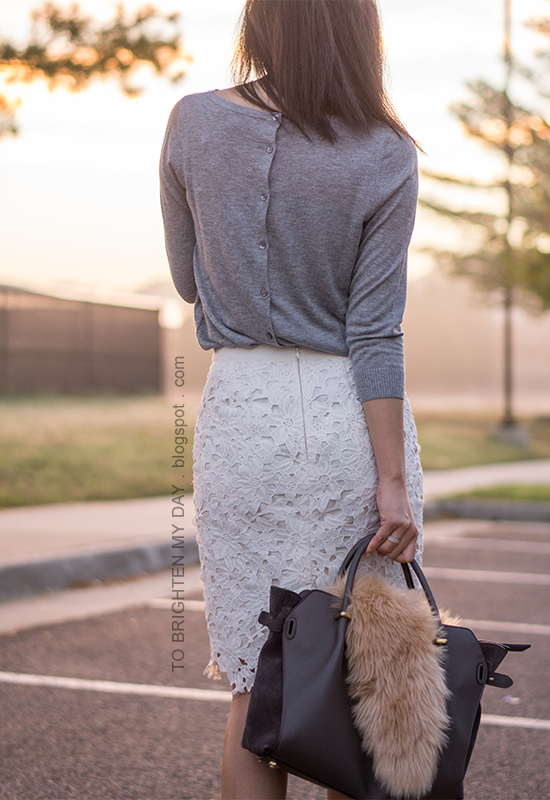 gray button back sweater, white floral lace pencil skirt, gray tote bag accessorized with faux fur scarf