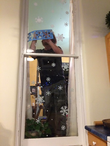 stenciling snowflakes on the dining room windows