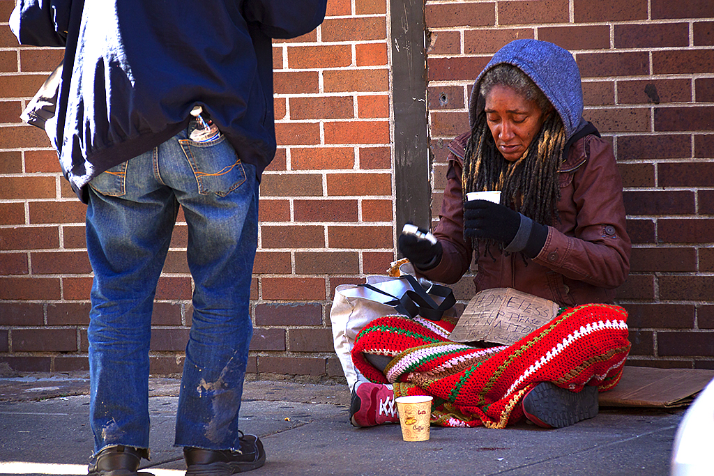 Man giving homeless woman coffee on 10-31-16--Chinatown