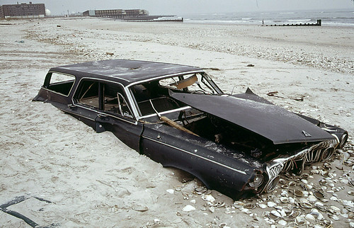 Welcome to New York, 1973 style! Half buried early 1960s Dodge Polara station wagon on the beach at the ocean side of Breezy Point in Queens. Abandoned apartment building at left distance. | by wavz13