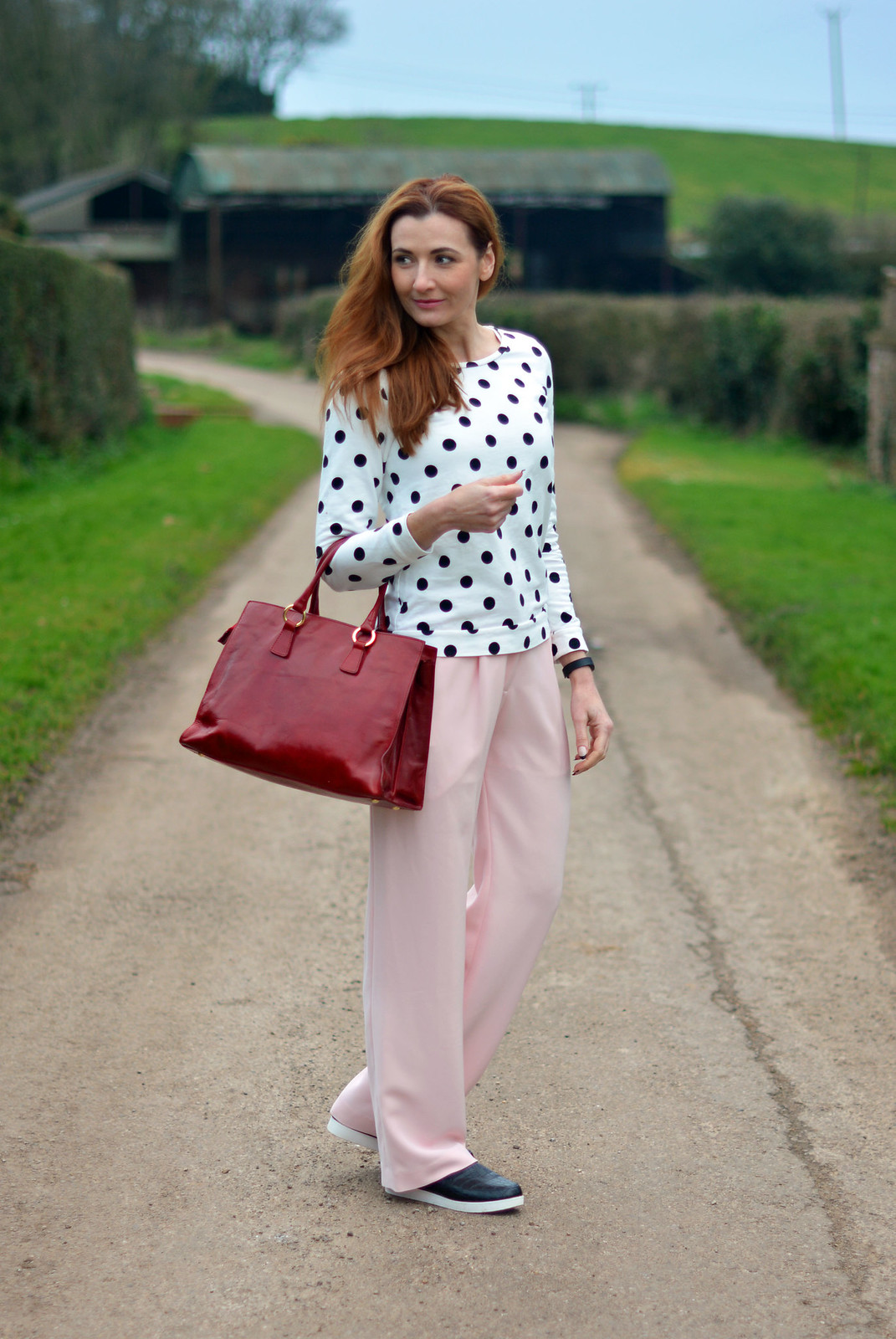 Black & white polka dot sweatshirt, pastel pink wide legged trousers, black slip on sneakers, cherry red tote