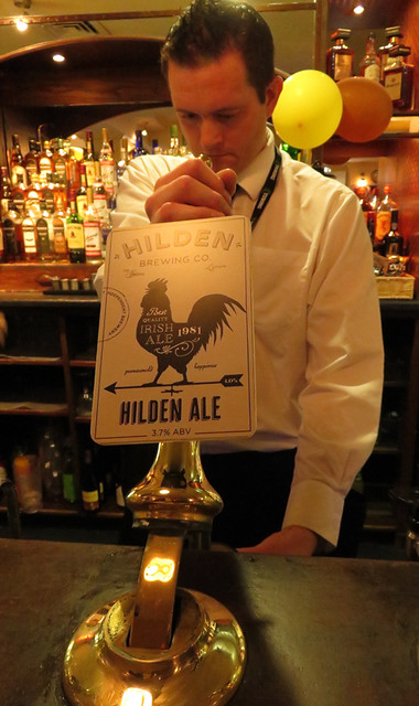 Pouring a Hilden beer at the Central Bar in Carrickfergus, a town on the Coastal Causeway Route of Ireland, UK