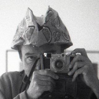 reflected self-portrait with Zeiss Tenax II camera and citrus themed hat (cropped)