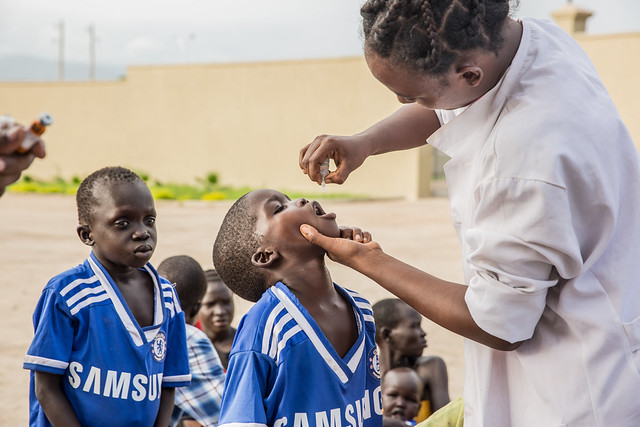 Kumeshi Kenna, clinical nurse from Gambella Bureau of health gives polio and measles vaccination to the newly arrived children at the temporary Gambella Regional state president's guest house.