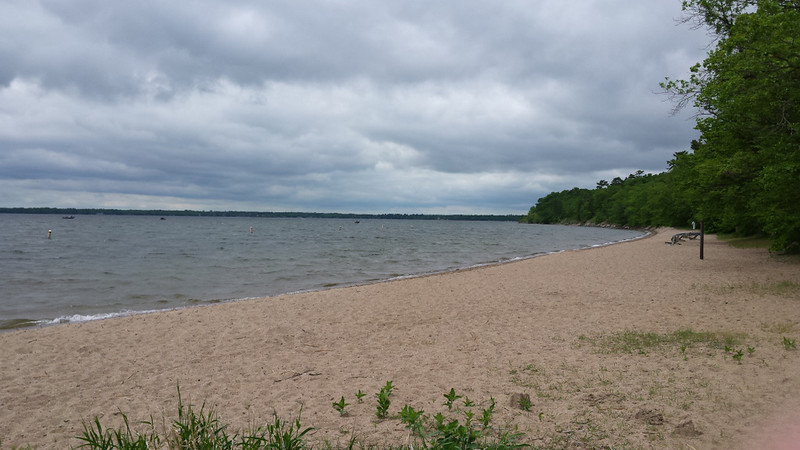 lake with a sandy beach on a cloudy day