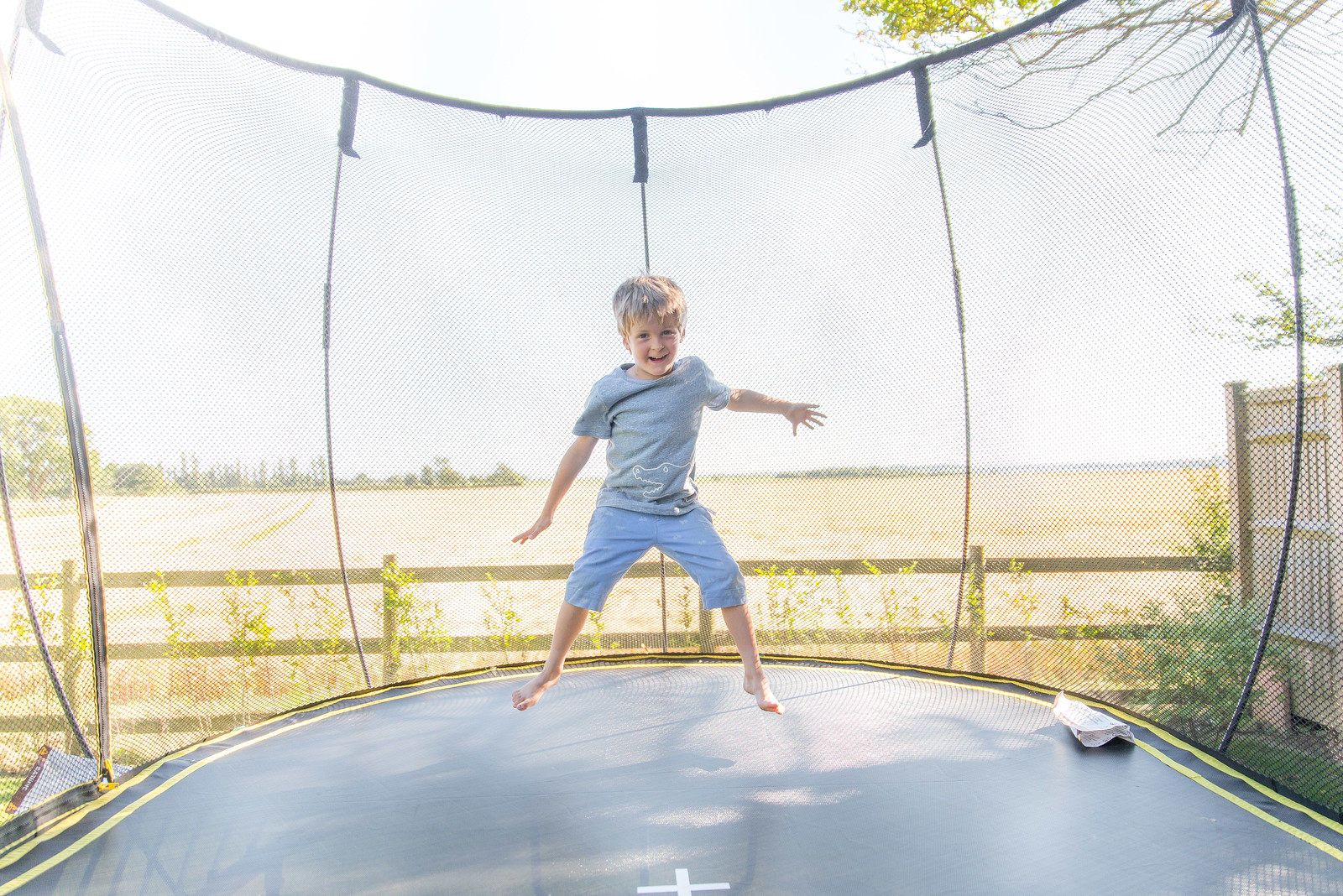 How to take great photos of your kids on the trampoline this summer - This photo was taken using a clever trick which makes the safety net vanish in photos!