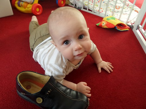 baby on the floor next to a shoe, looking at the camera in bafflement