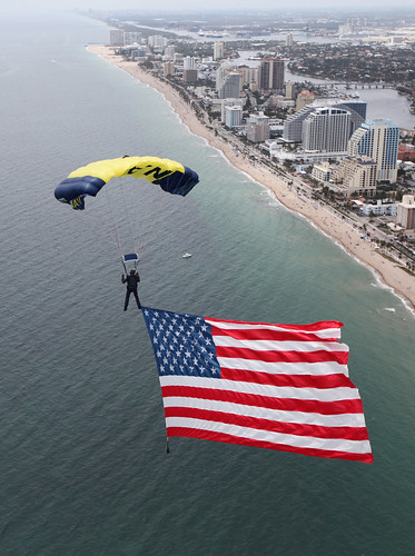 A SEAL on the U.S. Navy parachute demonstration team, the Leap Frogs, flys an 800-square-foot American flag during a rehearsal for the Lauderdale Air Show. | by Official U.S. Navy Imagery