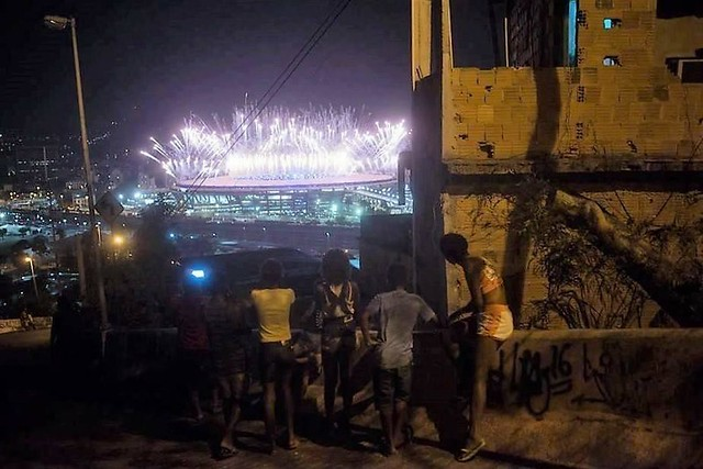 Residents of Mangueira favela watch the Olympics' opening-ceremony fireworks at Maracana stadium in Rio de Janeiro, Brazil
