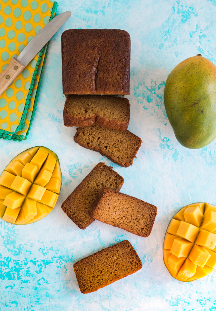 slices of mango bread next to half of loaf, two mango halves sliced into cubes