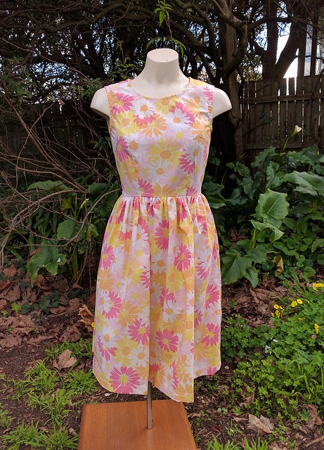 A fit and flare dress on a mannequin, in a vintage floral print.