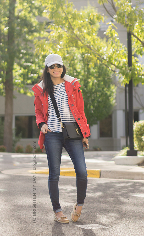 gray baseball cap, red performance jacket, striped top, black crossbody bag, skinny jeans, boat shoes